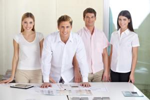 Vier lächelnde Mitarbeiter eines Architekturbüros stehen hinter einem Schreibtisch